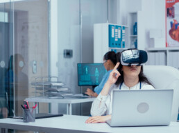 Young female doctor doing research in medicine with virtual reality headset on in private modern clinic. Nurse working in background and other medical staff walking by. Healthcare system hospital